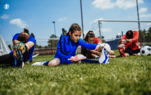 Young Athlete doing a hamstring stretch, wearing a blue football kit, sitting on the grass